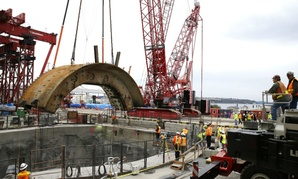 "A crane lifts a 270-ton portion of ""Bertha,"" the massive boring machine cutting a highway tunnel under Seattle."