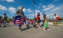 Children, parents, and employees of the Child Development Center East march around the parking lot during a parade in honor of Flag Day on Hurlburt Field in 2013.