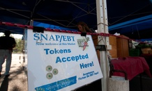 A sign touting use of SNAP benefits at a farmers market sits at a farmers market in Florida in 2012.