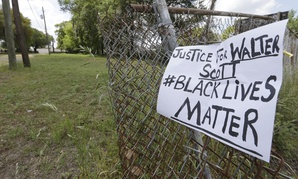 A sign calling for justice is attached to a fence near the site where Walter Scott was killed in North Charleston, S.C.