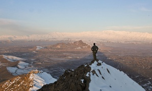 A coalition force member stands on top of a hill watching a snow-covered mountain range in Kabul province, Afghanistan.