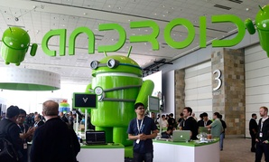 Visitors walk past the Android booth on the floor at Google I/O 2013 in San Francisco.