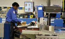 A TSA screener checks bags at Chicago's Midway International Airport during the 2014 holiday season.