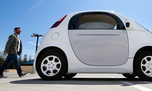 A reporter walks toward Google's new self-driving prototype car during a demonstration at the Google campus in Mountain View, Calif.