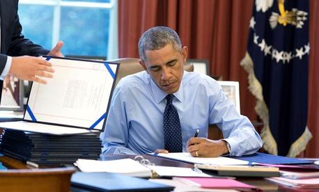 President Obama signs bills in the Oval Office in September 2014.