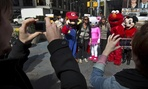 People have their photos taken with Super Mario, Hello Kitty, Elmo and Minnie Mouse characters in New York's Times Square, Tuesday, April 9, 2013.