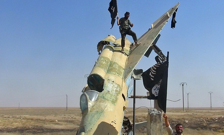 Fighters of the Islamic State wave the group's flag from a damaged display of a government fighter jet following the battle for the Tabqa air base, in Raqqa, Syria in 2014.