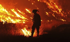 In this Aug. 3, 2015, file photo CalFire firefighter Bo Santiago lights a backfire as the Rocky fire burns near Clearlake, Calif.