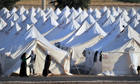 Refugees stand outside a camp on the Syrian-Turkish border in 2011.