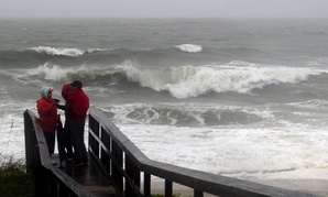 People watch the waves in a rainstorm at Atlantic Ocean at Carolina Beach, N. C., Friday, Oct. 2, 2015. Millions along the East Coast breathed a little easier Friday after forecasters said Hurricane Joaquin would probably veer out to sea instead of joinin