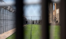 White House staff walk into Oklahoma's  El Reno Federal Correctional Institution in July.