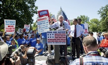 Democratic presidential candidate Sen. Bernie Sanders, I-Vt., joined by Rep. Keith Ellison, D-Minn., at right, and federal contract workers, speaks during a rally on Capitol Hill July 22 to push for a raise in the minimum wage.