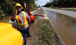 George Jenkins, with the South Carolina Department of Transportation, calls to officials asking whether to close Dorchester Road as floodwaters caused by high tide begin to flood the road again at Sawmill Branch Canal in Summerville, S.C., Thursday, Oct.