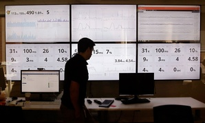 An employee in the software development department of DraftKings, a daily fantasy sports company, walks past screens displaying the company's online system stats in Boston in September.