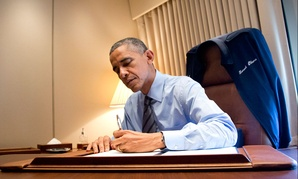 Barack Obama signs two presidential memoranda associated with his actions on immigration in his office on Air Force One in 2014.