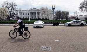 A Secret Service agent rides his bike on Pennsylvania Avenue outside the White House in April.