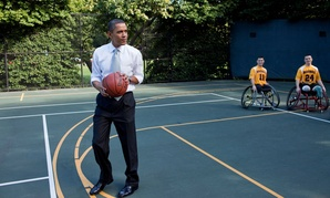 Barack Obama prepares to take a shot before watching a game played by members of the National Naval Medical Center's Marine Wounded Warrior basketball team on the White House basketball court in 2009.