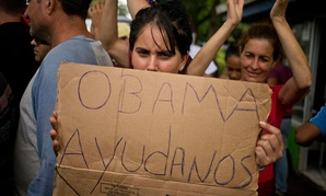 """A Cuban migrant holds a sign that reads in Spanish """"Help us Obama"""" during a protest at the Costa Rican border with Nicaragua on Monday."""