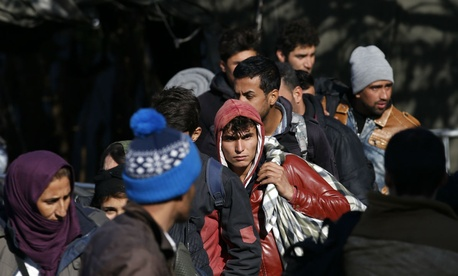 Refugees, such as these who await police processing in Serbia, have been fleeing the Middle East and streaming into Europe by the tens of thousands.