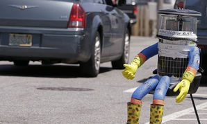 A car drives by HitchBOT, a hitchhiking robot in Marblehead, Mass.