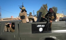 Islamic State militants patrol an Iraqi city in 2014.