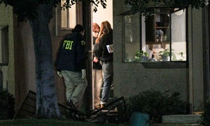 Agents search a home in connection to the shootings in San Bernardino Thursday.