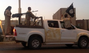 Islamic State militants parade in a commandeered Iraqi security forces vehicle in Mosul in 2014.