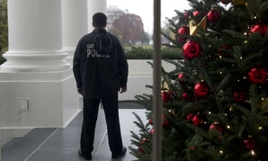 A member of the Secret Service Uniform Division looks out from the North Portico during a preview of the 2015 holiday decor at the White House in early December.