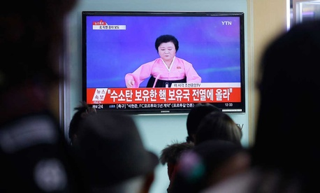 People watch a TV news program showing North Korea's announcement, at the Seoul Railway Station in Seoul Wednesday.