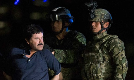 """Mexican drug lord Joaquin """"El Chapo"""" Guzman is escorted by army soldiers to a waiting helicopter in Mexico City Friday."""