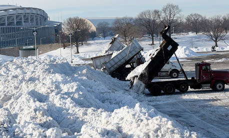 Trucks dump their loads of snow in the parking lots of RFK Stadium Monday.