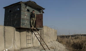 An Afghan airman stands at his security post near Forward Operating Base Oqab in Kabul, Afghanistan.