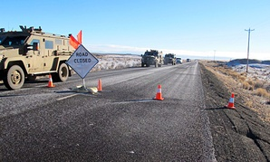 A convoy of armored vehicles and SUVs rolls past a barricade on the road near the Malheur National Wildlife Refuge on Jan. 30.