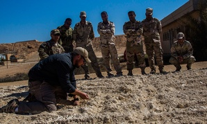 A civilian contractor works with Iraqi soldiers in 2015.