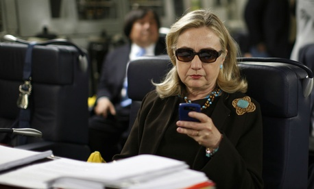 Hillary Clinton checks her Blackberry aboard a C-17 military plane in October 2011.