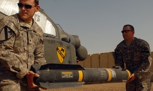 Spc. Scott Shaver (left) and Spc. Bret Gibson, haul a Hellfire missile to load onto the mounting bracket of an AH-64D Apache helicopter in 2009