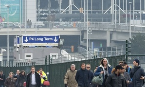 People walk away from the broken windows at Zaventem Airport in Brussels after an explosion on Tuesday.
