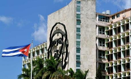 A Cuban flag flies near Che Guevara mural adjacent to Jose Martí plaza in Havana.