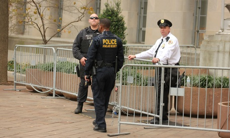 Security officers stand outside the Justice Department during a rally.
