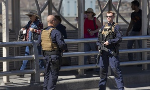 Pedestrians cross into Juarez, Mexico as U.S. Customs and Border Protection officers of the Special Response Team unit, patrol the Paso del Norte Port of Entry in El Paso, Tuesday, Feb. 16, 2016.