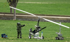 A member of a bomb squad examines the felled gyrocopter after it crashed in April 2015.