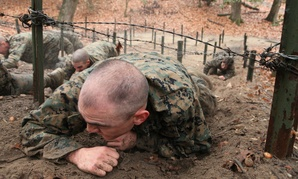 A Marine enrolled in Officer Candidate School low-crawls under a barbed wire obstacle on the Montford Point Challenge obstacle course at Marine Corps Base Quantico, Va.