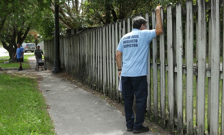Giraldo Carratala, an inspector with the Miami- Dade County mosquito control unit, looks through a fence into the back yard of a home while doing a routine inspection earlier this month.