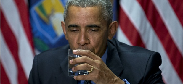 President Obama takes a sip of filtered water during a press conference in Flint on Wednesday.
