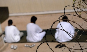 A small group of detainees housed in Guantanamo sit on prayer rugs in 2009