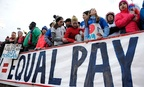 Fans stand behind a large sign for equal pay for the women's soccer team during an international friendly soccer match between the United States and Colombia in April.
