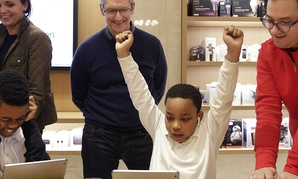 Third-grader Jaysean Erby raises his hands as he solves a coding problem as Apple CEO Tim Cook watches from behind during a coding workshop at an Apple Store, in New York.