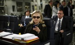 Then-Secretary of State Hillary Rodham Clinton checks her Blackberry from a desk inside a C-17 military plane bound for Tripoli, Libya.