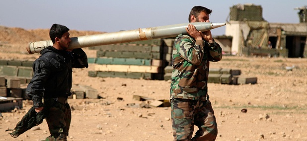 Two soldiers from the Syrian army carry a rocket to fire at Islamic State group positions in the province of Raqqa, Syria in February.