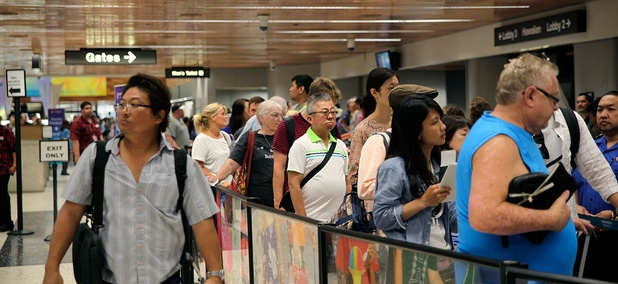 Travelers wait in security checkpoint lines at Honolulu International Airport on Thursday.